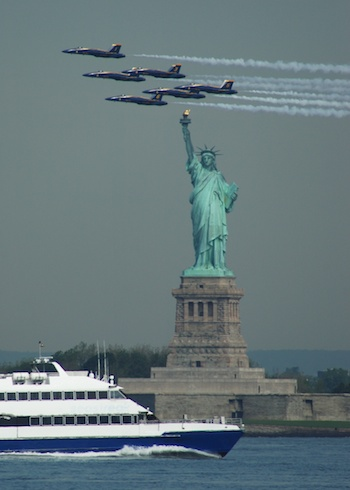 The US Navy Blue Angels pass in formation just above the Statue of Liberty in view from Red Hook. ©Mark D Phillips