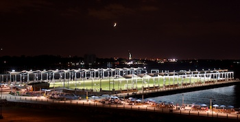 The soccer field on Pier 5 (multi-purpose playfields) at Brooklyn Bridge Park lit at night with the Statue of Liberty and Moon overhead. The Picnic Peninsula is at right with blue umbrellas. ©Mark D Phillips