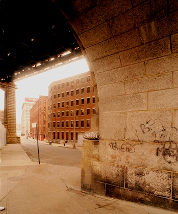 Under the Manhattan Bridge overpass in DUMBO in 1999, warehouse buildings are being converted to loft apartments. ©Mark D Phillips